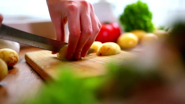 Weibliche Hände Schneiden Kartoffeln auf Holzbrett.