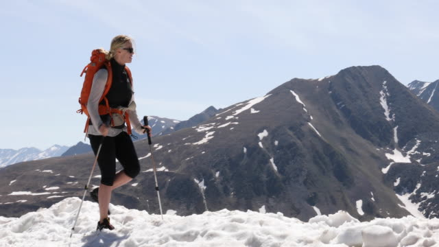 Female hiker ascends snowy ridge crest in mountain landscape