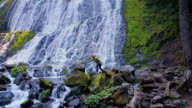 Female Hiker Climbing Over Rocks Beneath Massive Waterfall