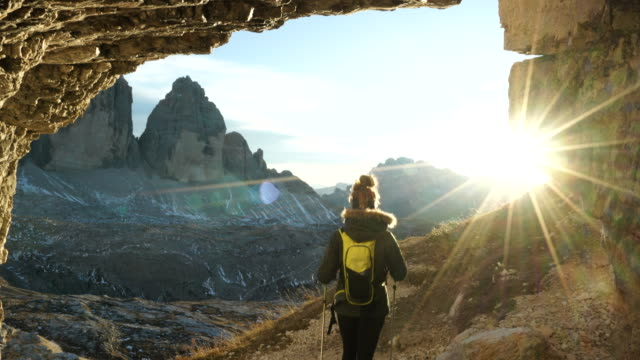 Female hiker exits mountain cave towards sunset, view of mountains below