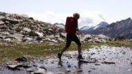 Female hiker hops between stepping stones in creek, mountains