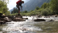 Female hiker hops onto rock in mid-stream, takes phone pic