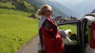 Female hiker leaves car by roadside to begin hike