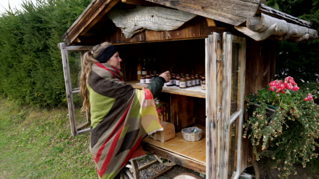 Female hiker purchasing local products along mountain trail