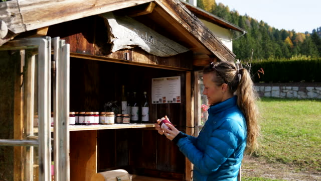 Female hiker purchasing local products at small store along mountain trail