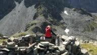 Female hiker relaxes in impromptu rock shelter