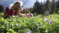 Female hiker relaxes in mountain meadow, amongst wildflowers
