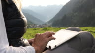 Female hiker relaxes in mountain meadow with digital tablet
