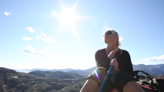 Female hiker relaxes on rock crest above hills, looks off