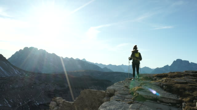 Female hiker stops at rock viewpoint to watch sunset