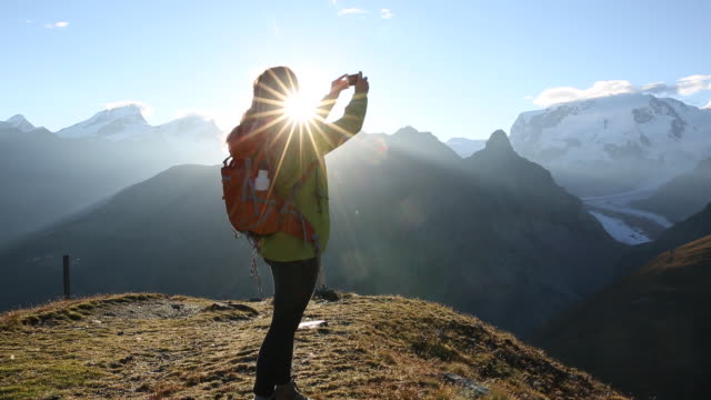 Female hiker takes smart phone pic of sunrise above distant mountains, glaciers.