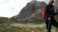 Female hiker walks along alpine trail, in mountains