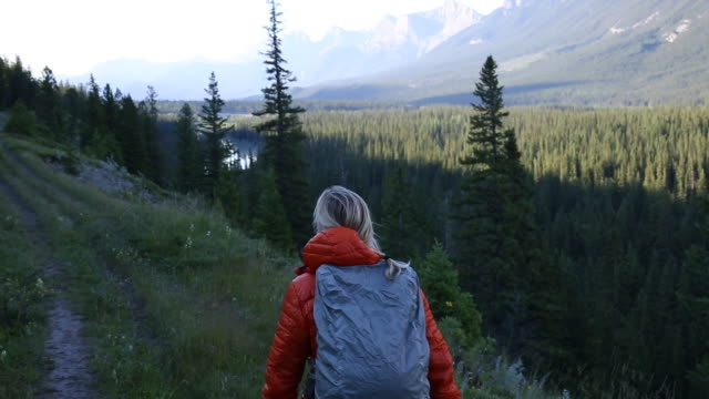 Female hiker walks along mountain trail, early morning