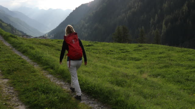 Female hiker walks along track above mountain ranges