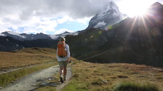 Female hiker walks along trail below Matterhorn, sunrise.