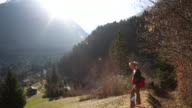 Female hiker walks up meadow slope, looks towards mtns