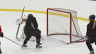 Female ice hockey goalie saving puck with butterfly technique