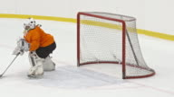 Female ice hockey goalie saving puck with her shoulder