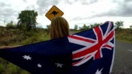 Female in Australia holding flag near kangaroo sign