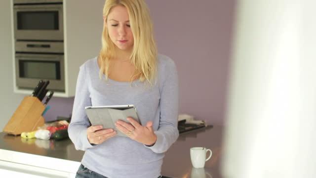 Frau in der Küche, die mit digitalen tablet