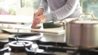 Female in kitchen preparing food looking into pan