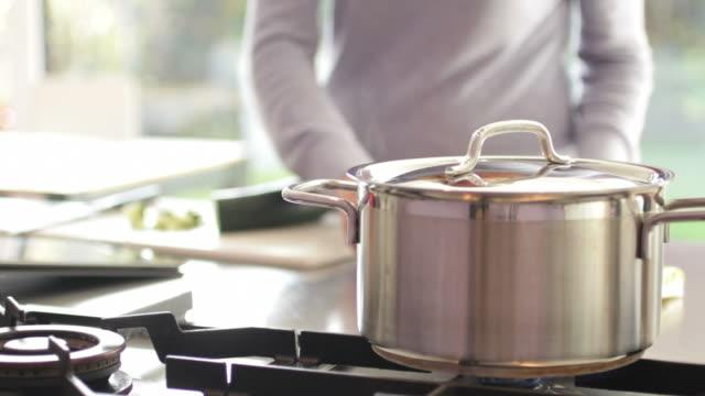Frau in der Küche putting pasta in pan von kochendem Wasser