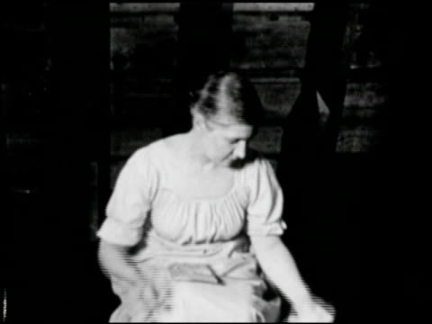 Female in long dress carrying bowl of fleece sitting down carding the fleece preparing for spinning MS Yarn on spinning wheel MS Female handspinning...