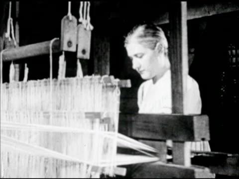 Female in long dress working on large freestanding hand loom CU Textile pattern on loom Americana artisan