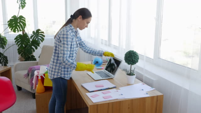 Female in shirt and gloves dusting laptop