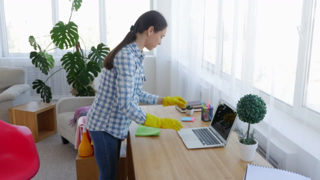 Female in yellow rubber gloves cleaning laptop