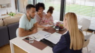 Female insurance agent advising young couple at their home