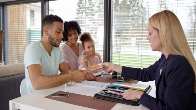 Female insurance agent shaking hands with family in their house
