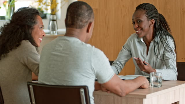 Female insurance agent talking to a multi ethnic couple in their home