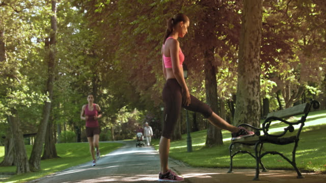 DS Female jogger stretching her legs on the park bench