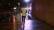 TS Female jogging in the city on a rainy night