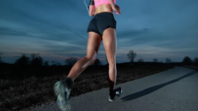 SLO MO weibliche Joggen auf ländliche Straße in der Abenddämmerung