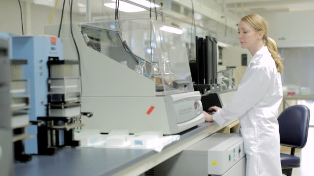 MS POV Female lab technician monitoring samples in shaking incubator at Cancer research Healthcare medicine Industry DNA sequencing Laboratory / Vancouver, BC, Canada