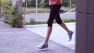 SLO MO TS Female legs running along city street