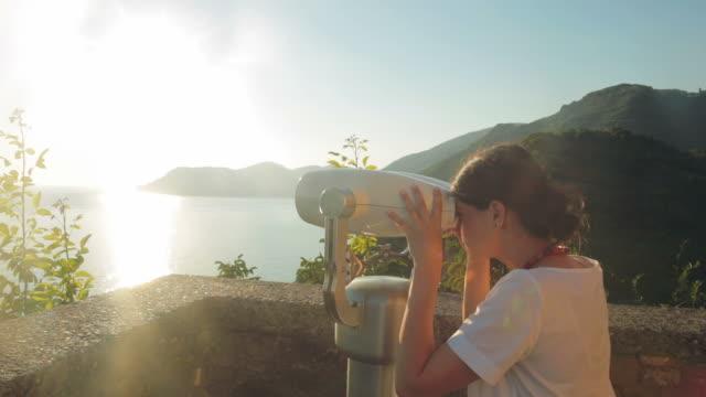Female looking through stationary binoculars.