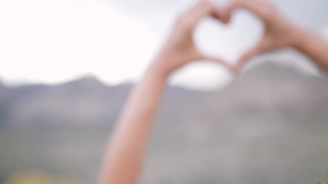 Female making heart shape symbol