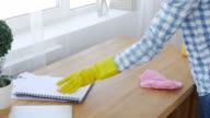 Female making order on the table with mop and spray