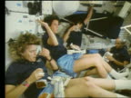 Female male astronauts eating in Space Shuttle Atlantis