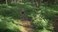 AERIAL Female marathon competitor running on a trail through the forest