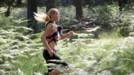 SLO MO DS Female marathon participant running through forest