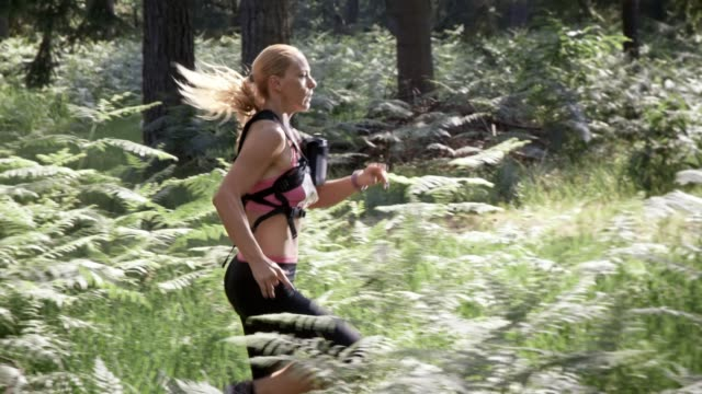 SLO MO DS Female marathon participant running through forest