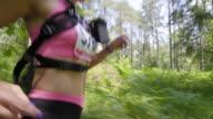 TS Female marathon runner running through forest