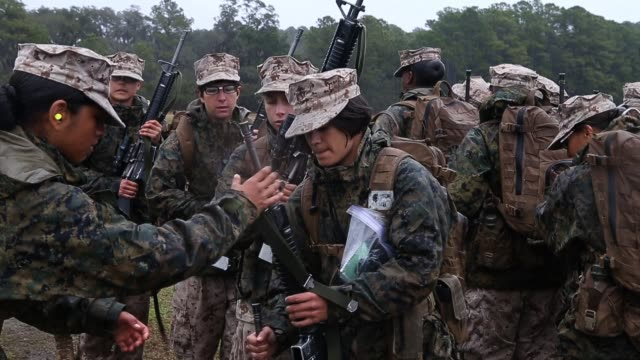Female Marine recruits inspect their rifles while on the rifle range during boot camp February 25 2013 at MCRD Parris Island South Carolina Women...