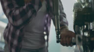CU. Female mechanic cranks ratcheting socket wrench in auto body shop.