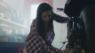 Female mechanic polishes motorcycle in sunlit automotive garage.