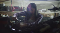 Female mechanic works on motorcycle with ratcheting socket wrench in automotive repair shop.
